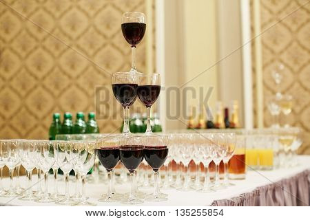 pyramid of glasses with red wine on table