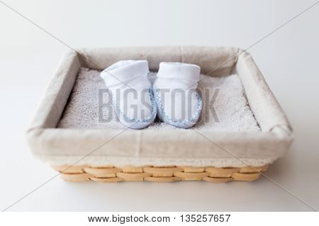 clothing, babyhood, motherhood and object concept - close up of white baby bootees for newborn boy on towel in basket