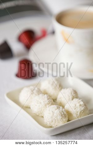 Close-up of white homemade healthy ball sweets with a cup and coffee capsules on the table. Sweet breakfast or snack. Coffee break. Raw coconut candies.