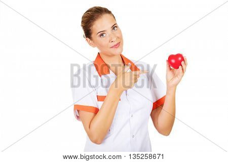 Female doctor or nurse holding a toy heart and pointing at them