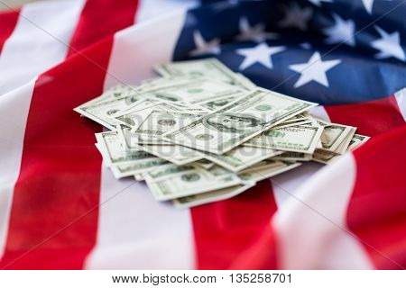 budget, finance and nationalism concept - close up of american flag and dollar cash money