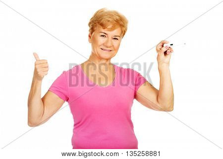 Senior woman shows thermometer and gesturing OK