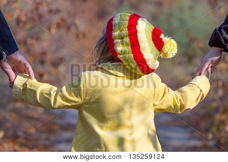 Two Generation Family Walking in Autumnal Forest Father Mother Holding Hands of Little Baby Girl Bright Yellow Clothing Coat and Cap Close Up Rear View