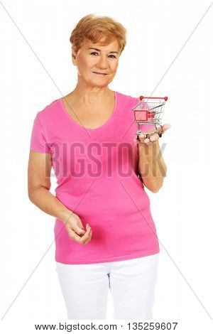 Senior smiling woman holding small trolley