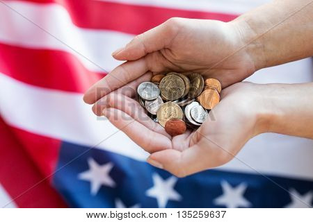 finances, money, crisis, investment and state budget concept - close up of hands with coins over american flag