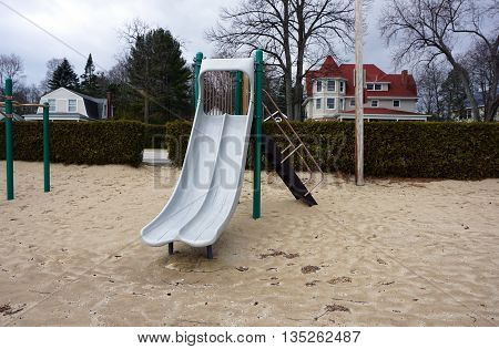 Children may slide down the slide, and play on other playground equipment, at the Zorn Park Beach in Harbor Springs, Michigan.