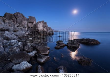 Colorful night landscape with full moon lunar path and rocks in summer. Mountain landscape at the sea