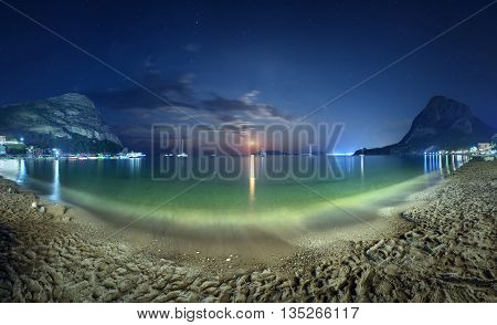 Beautiful night landscape at the seashore with yellow sand full moon mountains and lunar path. Moonrise. Panoramic view. Vacations on the beach at the sea.