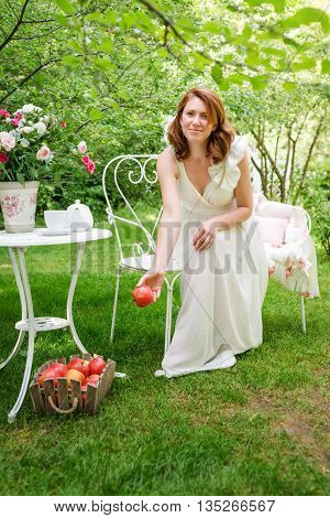 Pretty woman havig fun in the summer garden. Redhead woman with box of apples. Outdoor celebration summer garden tea party