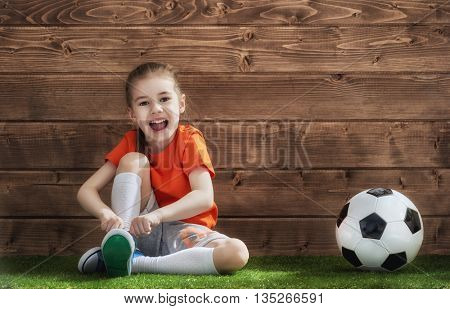 Cute little child dreams of becoming a soccer player. Girl plays football.