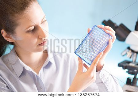 Scientist holding an open 96 well plate with samples, laboratory assistant examining a PCR microplate in hand