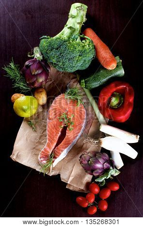 Raw Steak of Salmon on Parchment Paper and Heap of Raw Vegetables with Broccoli Artichokes Spring Onion Tomatoes Potato Red Bell Pepper and Lemon closeup on Dark Wooden background. Top View