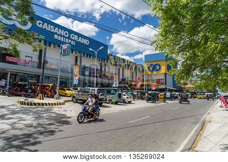 Moalboal. Cebu. Philippines - 03 april 2016: Mall Gaisano under blue sky near parking and road with motorcycle, bus and tricycle