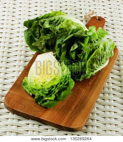 Fresh Crunchy Romaine Lettuce Two Full Heads and Half on Wooden Cutting Board closeup on Wicker background