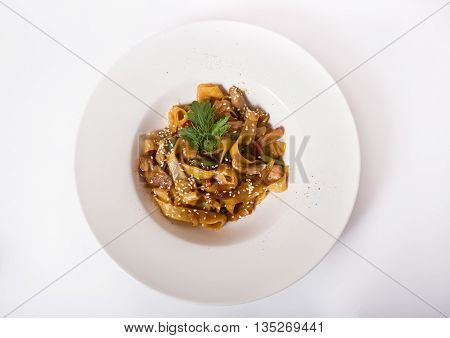 Chicken tagliatelle pasta with sesame seeds served on a white plate