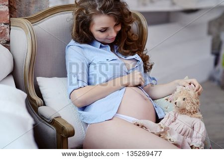 Beauty Pregnant Woman Indoors. Female Portrait Of Cute Lady. Close-up Beautiful Model Girl In Elegan