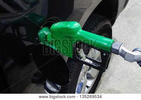 Green Handle Gas Pump Fueling Black Vehicle