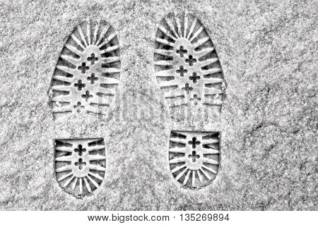 Clear deep footprints on white winter snow of a pair of boots or heavy soled shoes standing side by side pointing away from the camera overhead view