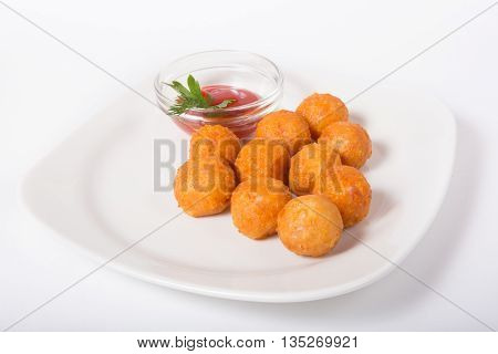 Fried potatoes balls served with tomato sauce