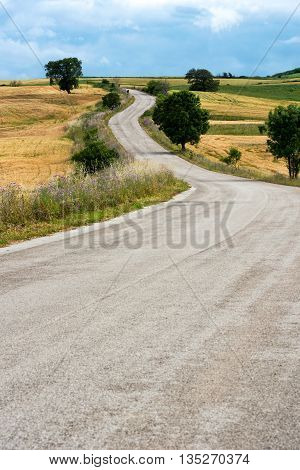 Deserted winding country road leading to low hills through open farmland and fields on a sunny day