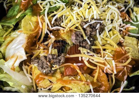 fresh taco salad of seasoned ground beef lettuce tomato and grated cheese
