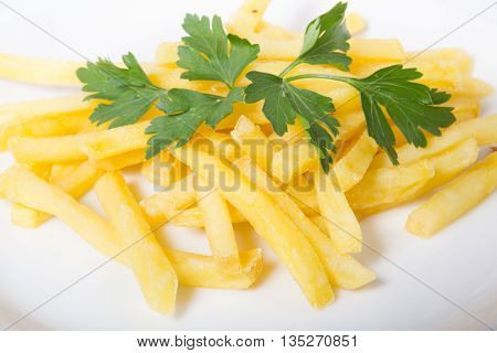 Fresh yellow french fries with parsley on a white plate