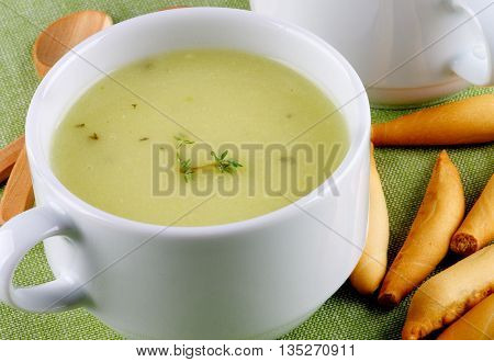 Delicious Asparagus Cream Soup in White Soup Cups with Bread Sticks and Wooden Spoons Cross Section on Green Napkin