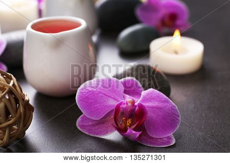 Beautiful spa set with massage oil and orchid on the table, close up