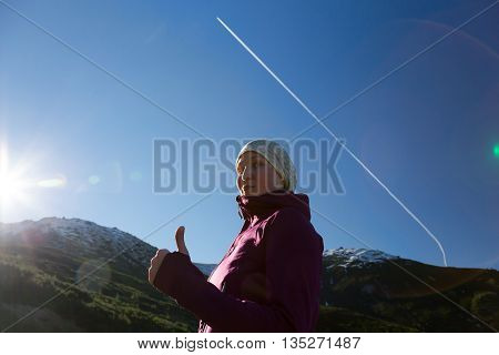 Sporty Dressed Female Outdoor Athlete Showing OK Sign with Blue Sky Raising Sun and Vapor Trail on Background