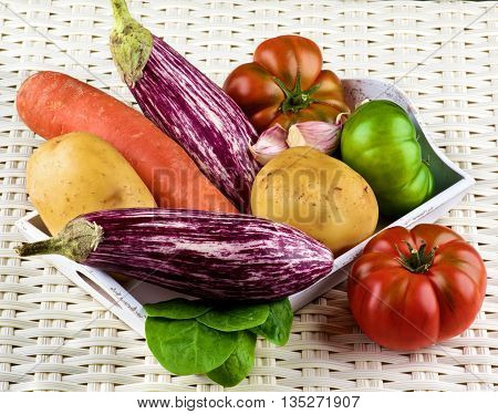 Arrangement of Fresh Raw Vegetables with Striped Eggplants Potatoes Green and Red Tomatoes Carrot Pink Garlic and Spinach into Wooden Tray closeup on Wicker background