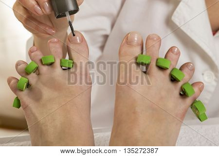 Woman's feet in pedicure toe separators at the nail salon. Beautician applying nail polish