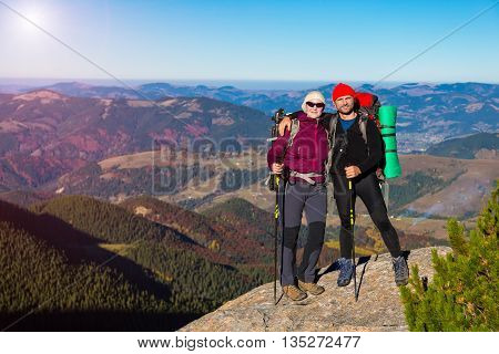 Male and Female Hikers with Backpacks Sporty Clothing and Trekking Poles Staying on High Rock Autumnal Colors Forest and Blue Sky Shining Sun on Background