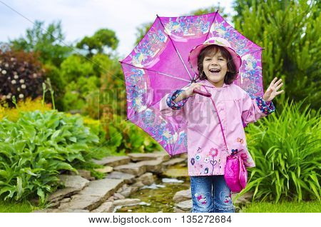 The little girl close in a pink hat and a raincoat. green background. Sweet toddler girl