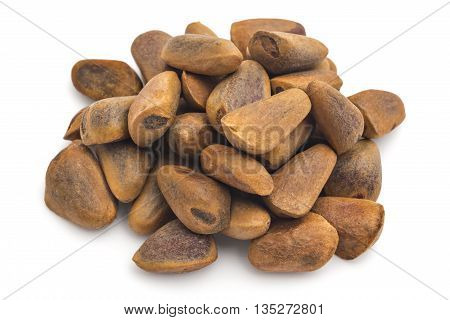 Pile of unpeeled cedar nuts on white background. Siberian cedar seeds, Pinus sibirica.