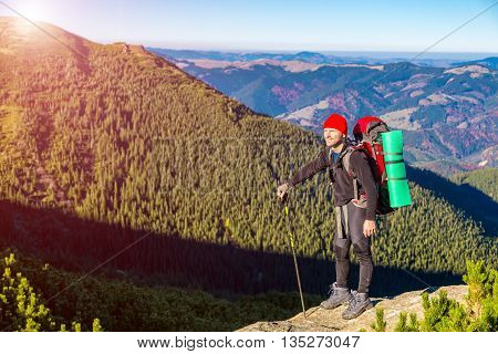 Person with Hiking Backpack Sporty Clothing and Trekking Poles Staying on High Rock with Mountain View and Blue Sky Shining Sun on Background