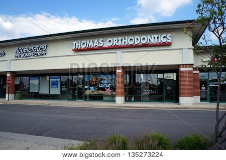 NAPERVILLE, ILLINOIS / UNITED STATES - JULY 23, 2015: One may have orthodontic work done at Thomas Orthodontics, in a Naperville strip mall.