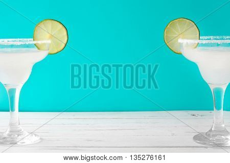 Margarita cocktail on a white wooden table and blue background