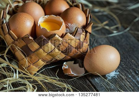 Fresh farm eggs in a basket on a wooden rustic background
