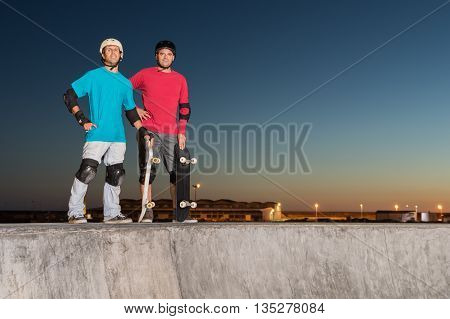 Two skateboarders standing near a concrete pool at skatepark on a beatiful sunset.