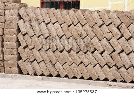 Adobe bricks stacked diagonally against a building