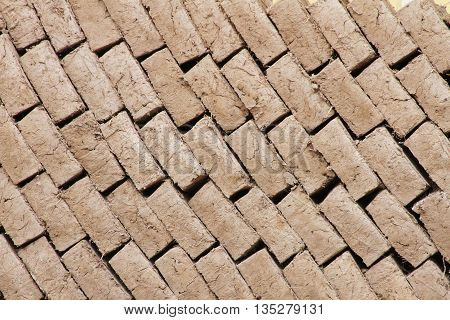 Background of newly dried adobe bricks stacked in a diagonal pattern
