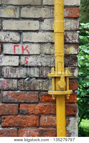 wall of old dilapidated shabby brickwork of red brick with yellow gas pipeline foreground closeup