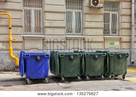 four blue and green color plastic dumpsters on the city street near building in Moscow