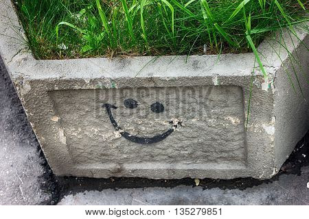 black graffiti smile symbol on square grey concrete flower bed with green grass in it on the street of Moscow Russia