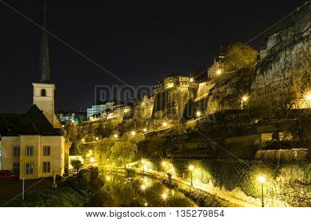 Sykline of Louxemburg City at night with a view over the Bockfelsen and reflections of the streetlights in the river Alzette.