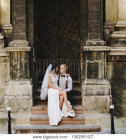 Bride sitting on the lap of the groom against the background of an old building