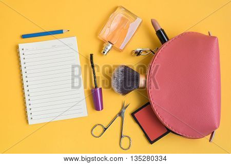Top view of pink cosmetic bag consist of makeup brush lipstick brush on scissors mascara eyelash curler perfume notepad and pencil on yellow background
