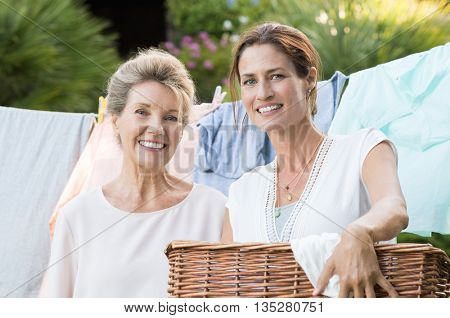 Daughter holding laundry basket standing in front of the laundry hanging. Old mother and daughter looking at camera with launfry on background. Happy women enjoying house work.
