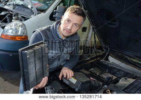 close-up of hand repairing car engine