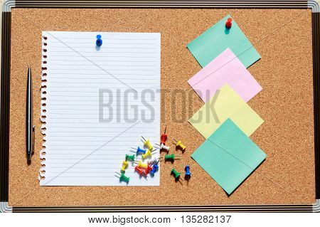 Top view of blank notebook on cork board with pen note and colorful pin.